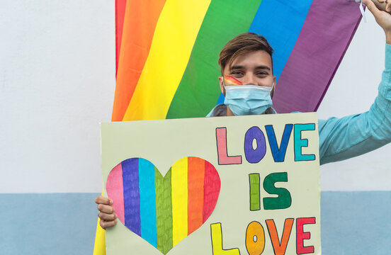 Happy man wearing face protective mask celebrating gay pride event during corona virus pandemic