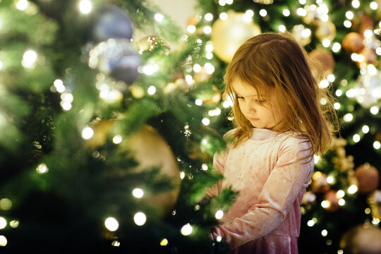 Portrait of a little girl holding ornament on Christmas tree