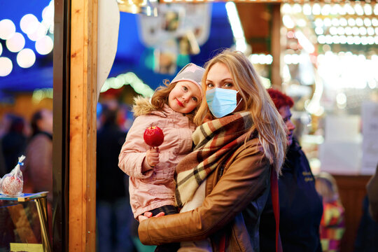Beautiful mother with medical mask and little daughter eating suger covered apple on Christmas market. Happy family. People with masks as protection against corona virus. Covid pandemic time lockdown.