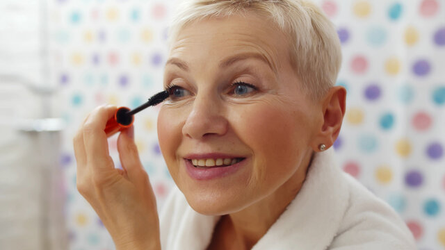 Mature woman putting mascara looking in mirror getting ready in morning