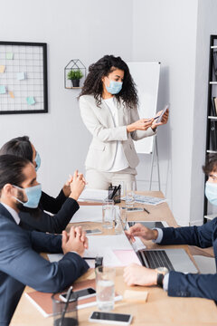 Hispanic businesswoman standing and pointing with pen at notebook during meeting with co-workers in office