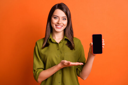 Photo portrait of smiling girl showing demonstrating empty space screen mobile phone isolated on vivid orange color background