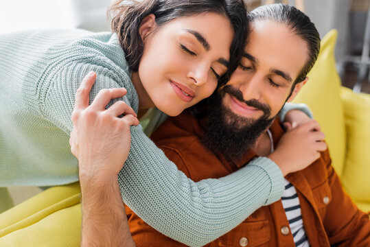 happy hispanic couple embracing and smiling with closed eyes at home