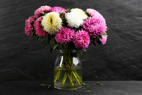 Beautiful asters in vase on table against black background. Autumn flowers