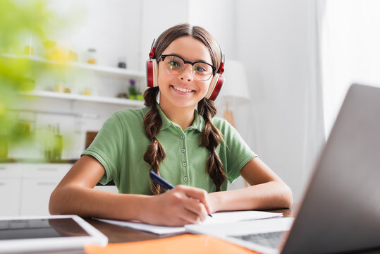 Cheerful hispanic girl looking at camera, while writing in copybook during online studying in kitchen on blurred foreground