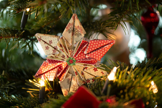 Decorated Christmas tree, real Nordmann fir in front of blurred background. Macro photography shows a 6 pointed star folded from paper.