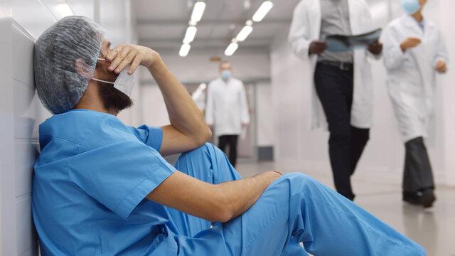 Upset and tired surgeon sitting on floor in hospital corridor