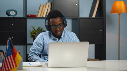Smiling african american man in wireless headphones studying foreign language through video call
