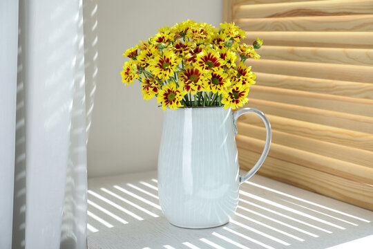 Vase with beautiful chrysanthemum flowers on white windowsill
