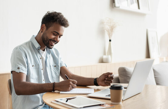 Young handsome man using laptop at home, Businessman or student working online on computer indoors, Freelance, online marketing, distance education, e-learning, home work and lockdown concept