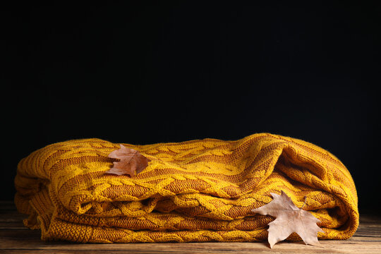 Orange knitted plaid with dry leaves on wooden table. Space for text