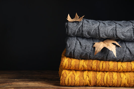 Grey and orange knitted plaids with dry leaves on wooden table, closeup. Space for text