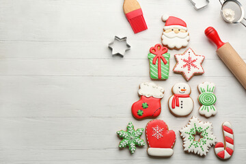 Kitchen utensils near Christmas tree shape made of delicious gingerbread cookies on white wooden...