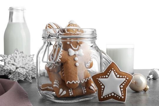 Tasty Christmas cookies and milk on grey table against white background, closeup