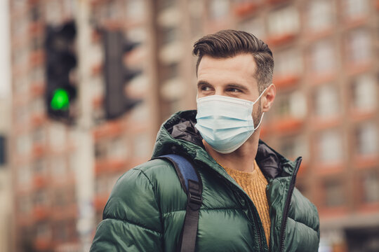 Photo of handsome positive good mood young man wear green windbreaker schoolbag face respirator walking outside city street