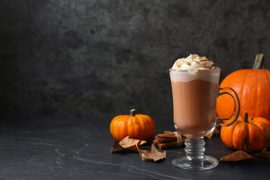 Delicious pumpkin latte on black slate table. Space for text