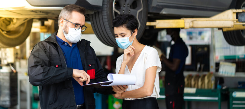 Mechanic man and woman customer wearing medical face mask protection coronavirus and check the car condition before delivery.