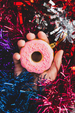 Hand holds christmas bauble in the shape of doughnut on the  holographic abstract purple, blue and red tinsel. Trendy vaporwave creative gradient.