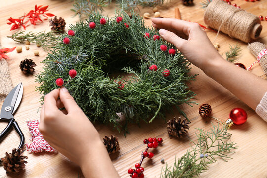 Florist making beautiful Christmas wreath with berries at wooden table, closeup