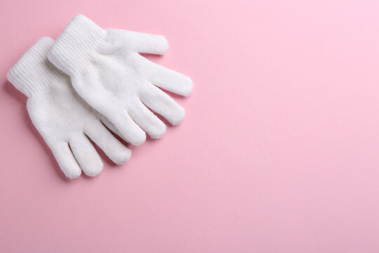 Pair of stylish woolen gloves on pink background, flat lay. Space for text