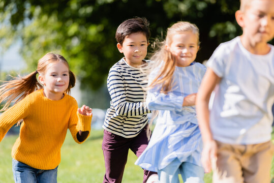 Smiling multiethnic children running near friends on blurred foreground outdoors