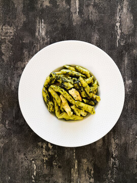 Pasta with pesto sauce and nuts on a the table
