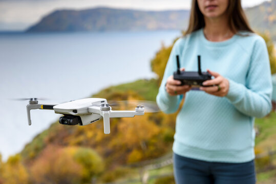 Blurred girl using dron. Flying copter on the blur autumn background
