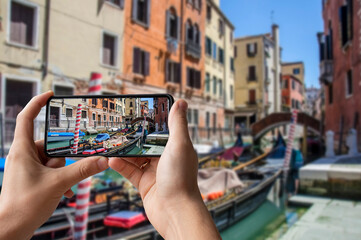 Tourist taking photo of traditional fancy decorated gondola in venetian water canal in Venice, Italy. Street in Venice