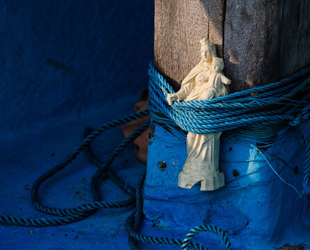 Close-up Of Virgin Mary Tied On Wooden Post In Boat
