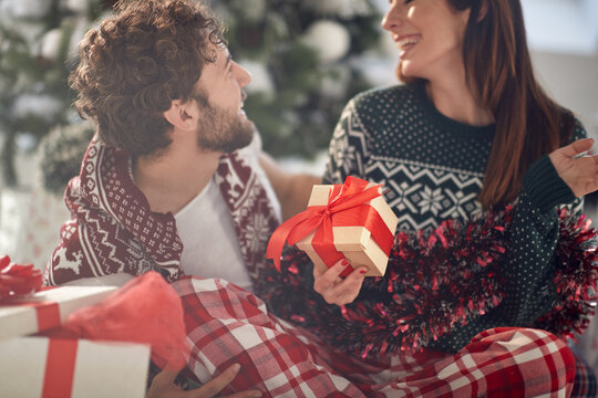 A young couple has romantic moments at home sharing Xmas presents. Christmas, relationship, love, together