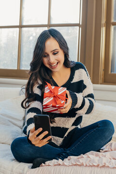 Portrait of a young woman celebrating with Christmas gift over the phone at home