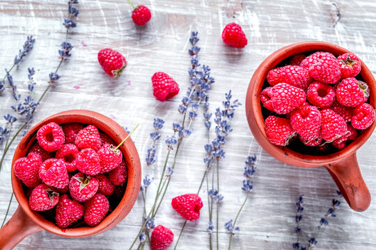 fresh raspberry and dry lavander in rustic design wooden background top view