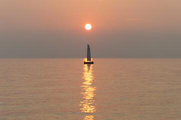 A sail boat peacefully sails at the horizon at suset time
