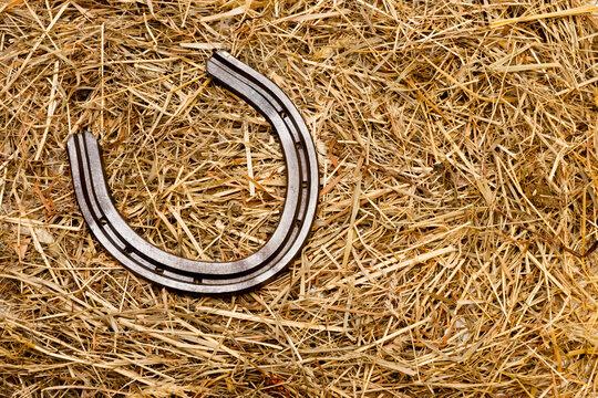 Altes Hufeisen aus Metall im Stroh