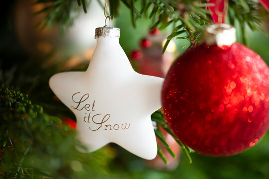 Decorated Christmas tree, real Nordmann fir in front of blurred background. Macro photography shows white star of glass. English text means: let it snow. A red ball has many bokeh bubbles.