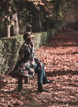 Mujer paseando por un parque al aire libre y con el móvil en las manos