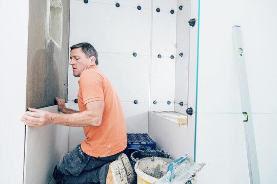Fliesenleger installiert großformatige Fliesen an der Wand. Haus Renovierung