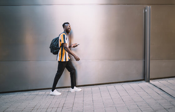 Side view of stylish hipster guy with travel backpack holding digital mobile phone and walking at urban street, millennial African American man in eyewear and earphones listening online music playlist