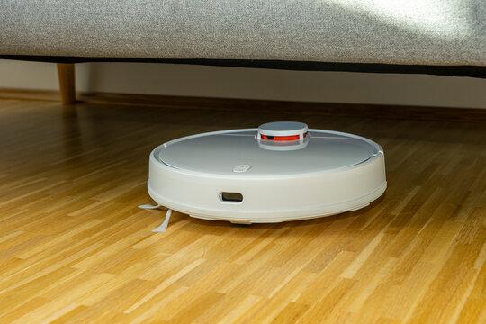 Weißer Staubsaugerroboter / Saugroboter reinigt im Wohnzimmer den Parkettboden / Laminat unter dem Sofa