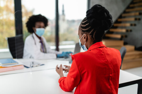 Female Afro American doctor talking with her patient behind protective glass. They wearing protective face masks as a virus pandemic protection. Coronavirus healthcare concept.