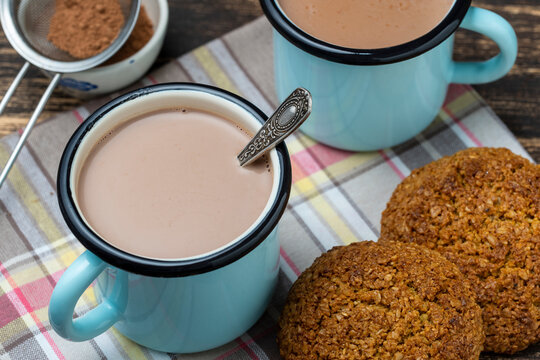 Hot cocoa drink and oatmeal cookies on the table.