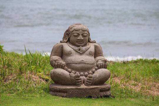 Meditating Buddha statue on tropical beach in Indonesia