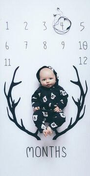 Portrait Of Baby Boy Lying On Calendar By Horns Drawn On It