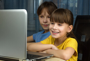 Two happy girls looking at the laptop and smile. Concept of home distance learning.