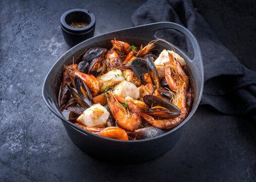 Traditioneller französischer Meeresfrüchte Eintopf  Bouillabaisse mit Fisch, Garmelen und Muscheln in Rotwein Sauce als close-up in einem Modern Design Topf mit Textfreiraum