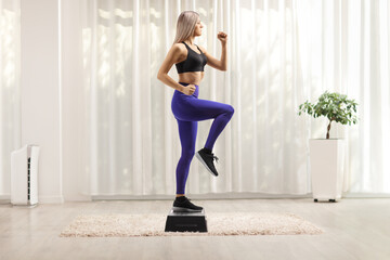 Young woman exercising step aerobic in a room