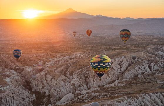 Hot air balloon flying over Cappadocia region, Goreme, Turkey. Great tourist attraction - sunrise balloning over Cappadocia valleys