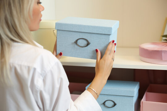 woman pulls out a beautiful storage box from the shelf of the cabinet