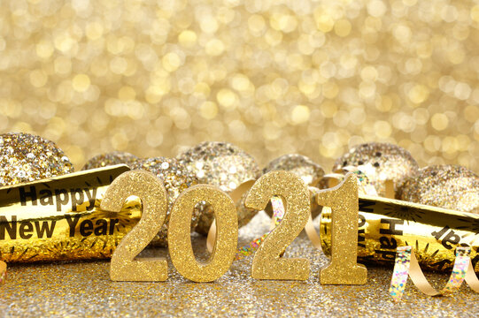 New Years Eve 2021 golden numbers and decorations with twinkling light background