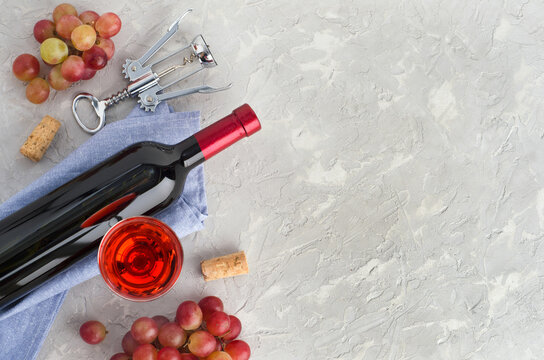 Wine glass, bottle of wine and bunches pink grape